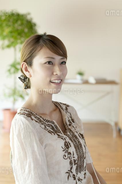 部屋で微笑む女性の写真素材 [FYI04547197]