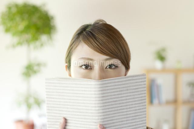 本で顔を隠す女性の写真素材 [FYI04547209]