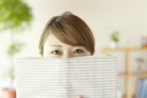 本で顔を隠す女性の写真素材 [FYI04547212]