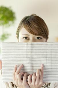 本で顔を隠す女性の写真素材 [FYI04547214]