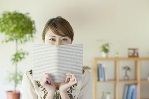本で顔を隠す女性の写真素材 [FYI04547215]