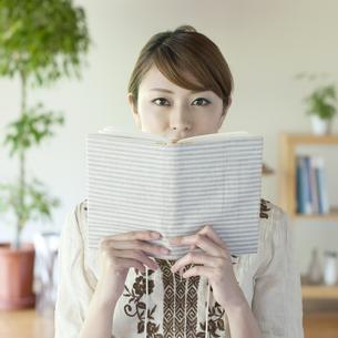 本で顔を隠す女性の写真素材 [FYI04547216]