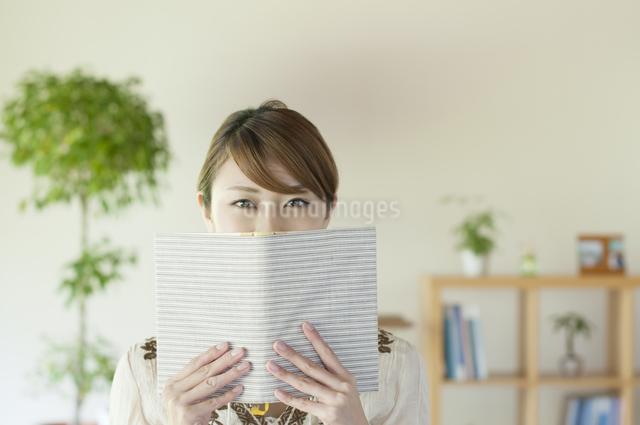 本で顔を隠す女性の写真素材 [FYI04547217]