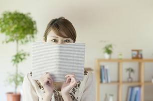 本で顔を隠す女性の写真素材 [FYI04547218]