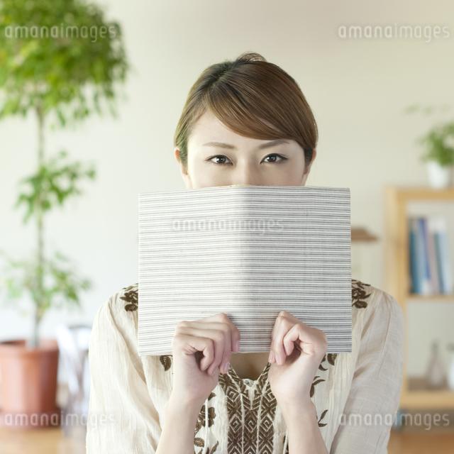本で顔を隠す女性の写真素材 [FYI04547219]