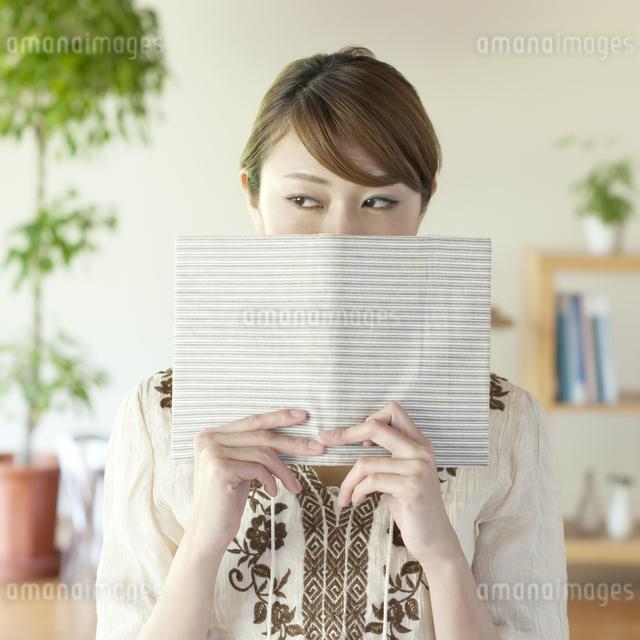 本で顔を隠す女性の写真素材 [FYI04547220]