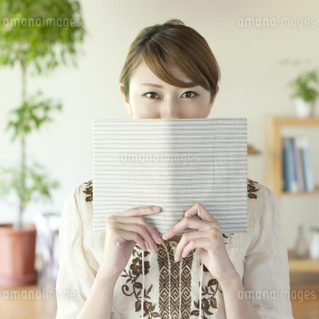 本で顔を隠す女性の写真素材 [FYI04547221]