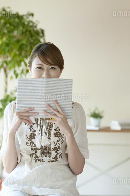 本で顔を隠す女性の写真素材 [FYI04547227]