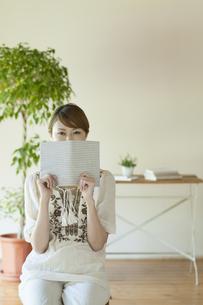 本で顔を隠す女性の写真素材 [FYI04547228]