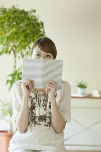 本で顔を隠す女性の写真素材 [FYI04547229]