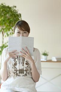 本で顔を隠す女性の写真素材 [FYI04547230]