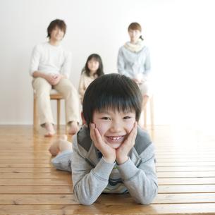 床に寝転び微笑む男の子と家族の写真素材 [FYI04547343]