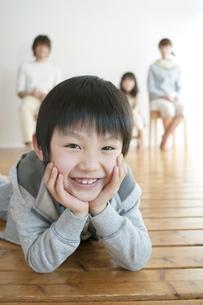 床に寝転び微笑む男の子と家族の写真素材 [FYI04547349]
