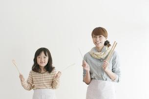 調理道具を持ち微笑む親子の写真素材 [FYI04547360]