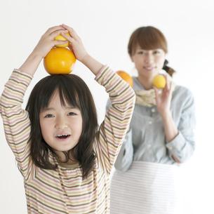 レモンとオレンジを持ち微笑む親子の写真素材 [FYI04547371]