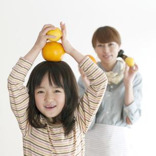レモンとオレンジを持ち微笑む親子の写真素材 [FYI04547372]