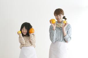 レモンとオレンジを持ち微笑む親子の写真素材 [FYI04547373]