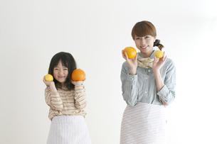 レモンとオレンジを持ち微笑む親子の写真素材 [FYI04547374]