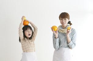 レモンとオレンジを持ち微笑む親子の写真素材 [FYI04547375]