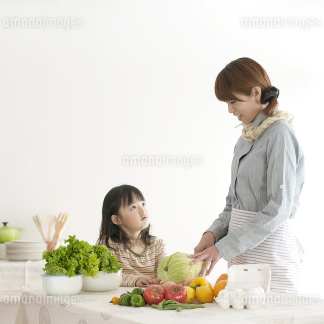 キッチンで料理をする母親と女の子の写真素材 [FYI04547376]