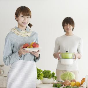 キッチンで食事の準備をするカップルの写真素材 [FYI04547385]