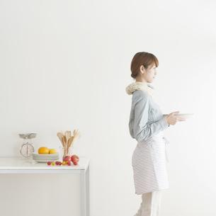 キッチンで食器を運ぶ女性の写真素材 [FYI04547399]