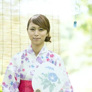 うちわを持ち微笑む浴衣姿の女性の写真素材 [FYI04547440]