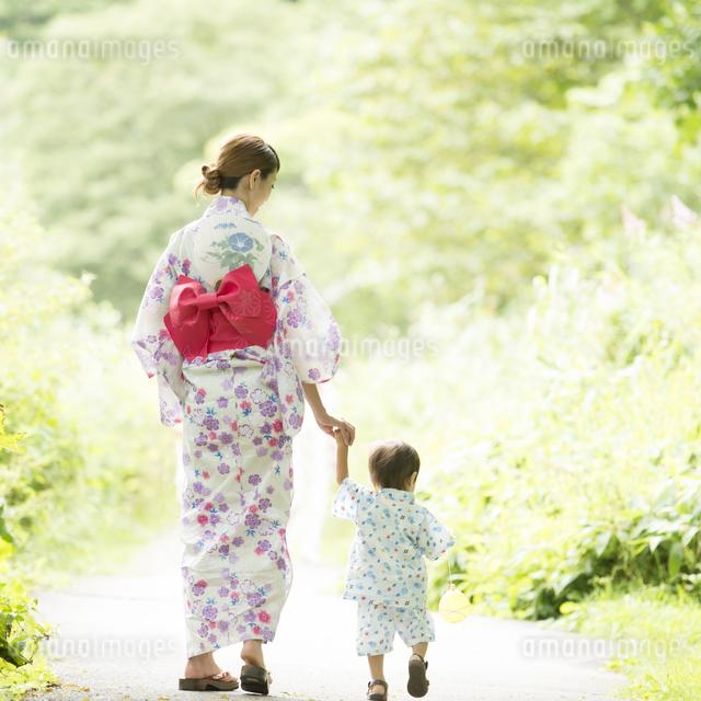 手をつなぐ親子の後姿の写真素材 [FYI04547454]
