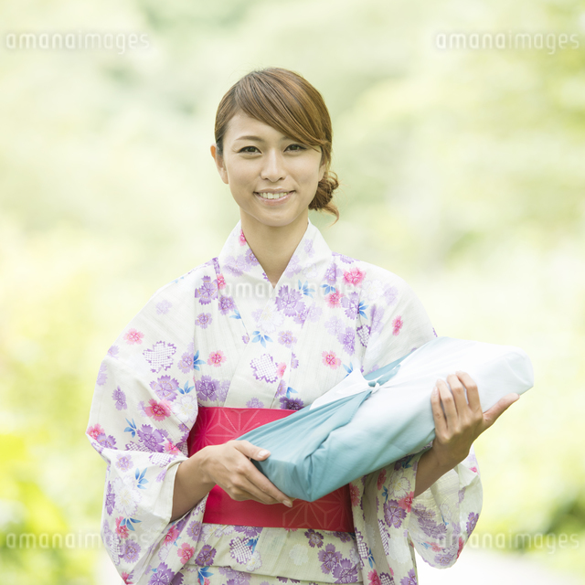 お中元を持ち微笑む浴衣姿の女性の写真素材 [FYI04547462]