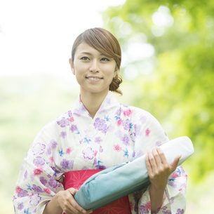 お中元を持ち微笑む浴衣姿の女性の写真素材 [FYI04547466]