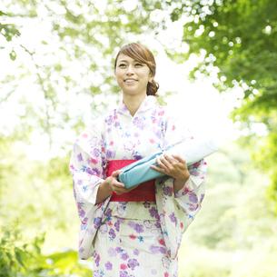 お中元を持ち微笑む浴衣姿の女性の写真素材 [FYI04547478]