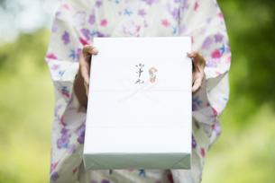 お中元を持つ女性の手元の写真素材 [FYI04547490]