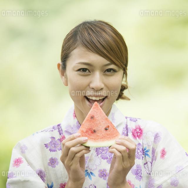 スイカを持ち微笑む浴衣姿の女性の写真素材 [FYI04547504]