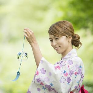 風鈴を持ち微笑む浴衣姿の女性の写真素材 [FYI04547536]