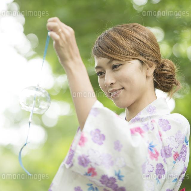 風鈴を持ち微笑む浴衣姿の女性の写真素材 [FYI04547538]