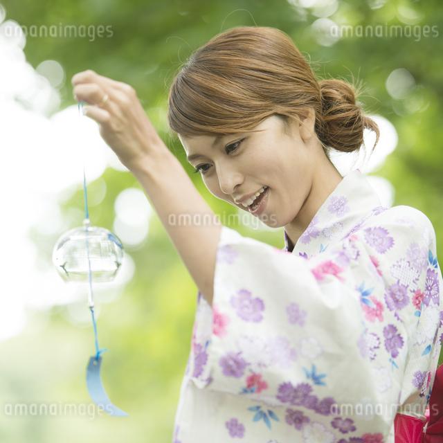 風鈴を持ち微笑む浴衣姿の女性の写真素材 [FYI04547541]