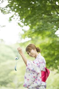 風鈴を持ち微笑む浴衣姿の女性の写真素材 [FYI04547544]