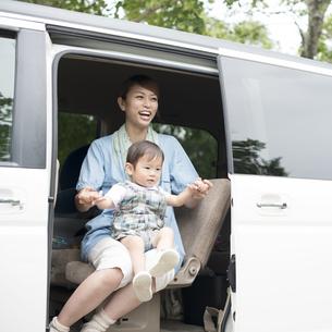 車の中で子供を抱き微笑む母親の写真素材 [FYI04547548]
