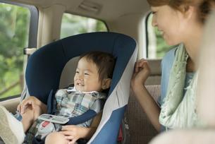 チャイルドシートに乗る子供と会話をする母親の写真素材 [FYI04547551]