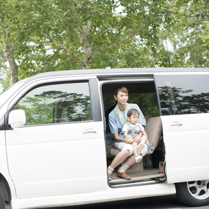 車の中で子供を抱き微笑む母親の写真素材 [FYI04547553]