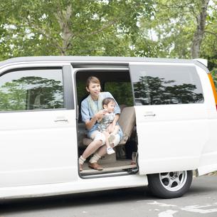 車の中で子供を抱き微笑む母親の写真素材 [FYI04547555]