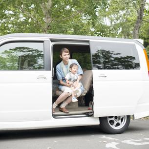 車の中で子供を抱き微笑む母親の写真素材 [FYI04547556]