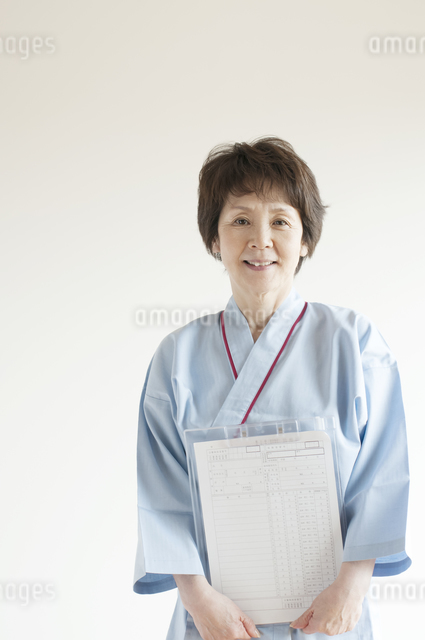 カルテを持ち微笑む患者の写真素材 [FYI04547711]