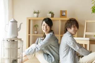 背中合わせに座り微笑むカップルの写真素材 [FYI04547714]