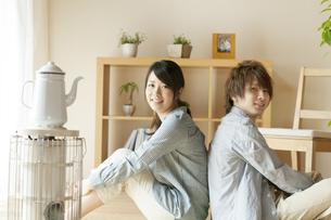 背中合わせに座り微笑むカップルの写真素材 [FYI04547715]