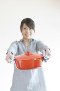 鍋を持ち微笑む女性の写真素材 [FYI04547767]
