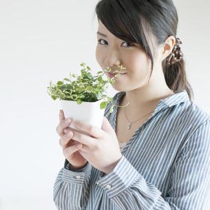 植物を持ち微笑む女性の写真素材 [FYI04547776]