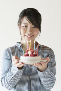 ケーキを持ち微笑む女性の写真素材 [FYI04547784]
