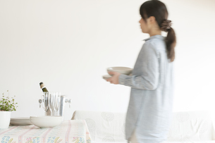 食器を運ぶ女性の写真素材 [FYI04547801]