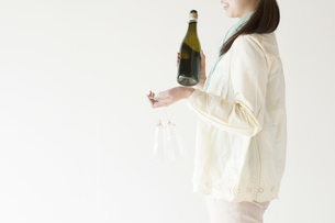 ボトルとシャンパングラスを運ぶ女性の写真素材 [FYI04547804]